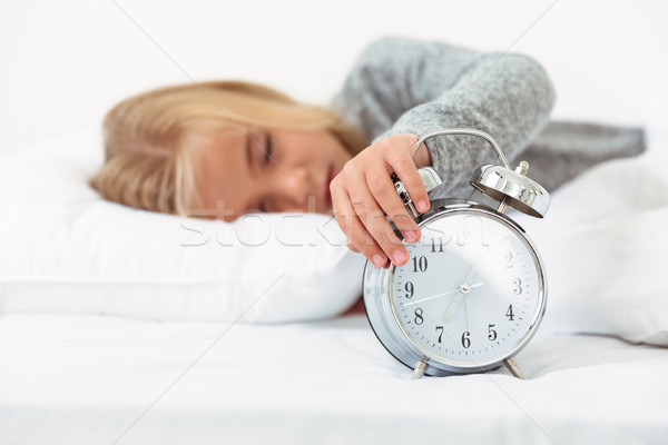 Close-up of sleepy little girl turned off alarm clock in her bed Stock photo © deandrobot