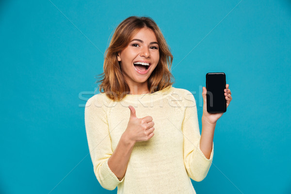 Happy woman in sweater showing blank smartphone screen Stock photo © deandrobot