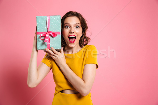 Stock photo: Happy exited pretty girl in yellow dress holding present, lookin