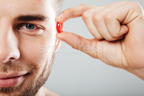 Close up portrait of a smiling man holding red capsule Stock photo © deandrobot