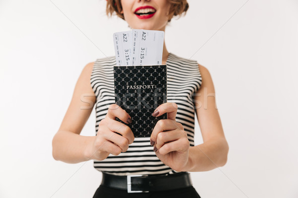 Close up of a young woman showing passport with tickets Stock photo © deandrobot