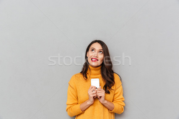 Pensive smiling woman in sweater holding smartphone and looking up Stock photo © deandrobot