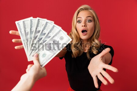 Shocked woman in sweater holding money and talking by smartphone Stock photo © deandrobot