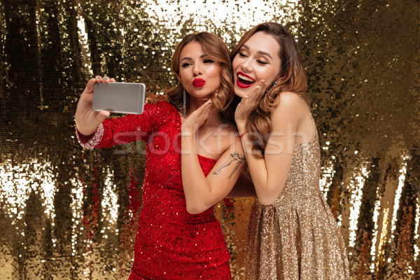 Portrait of two pretty lovely women in sparkly dresses Stock photo © deandrobot