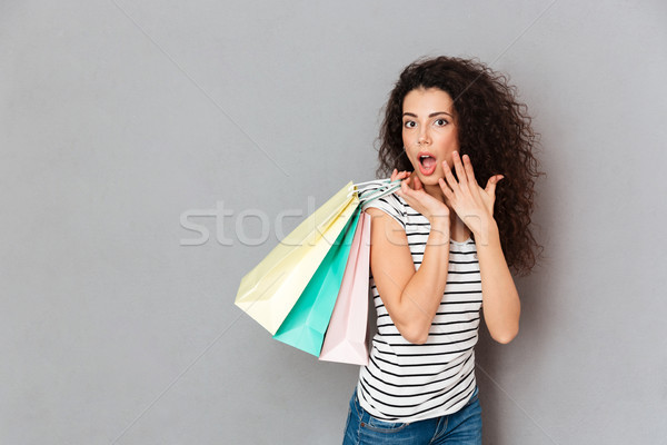 Pleased female shopaholic being excited with all purchases and p Stock photo © deandrobot