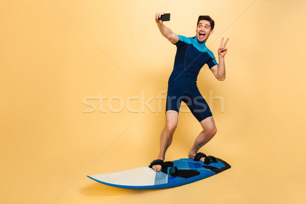 Full length portrait of a cheery young man Stock photo © deandrobot