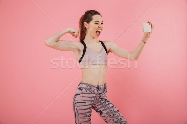 Stock photo: Confident pleased sportswoman making selfie on smartphone nd showing bicep