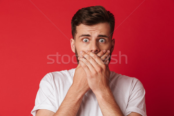 Scared young man covering mouth with hands Stock photo © deandrobot