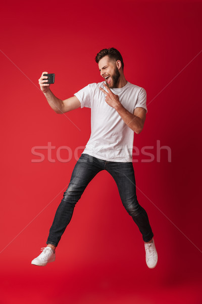 Excited young man make selfie by mobile phone jumping. Stock photo © deandrobot