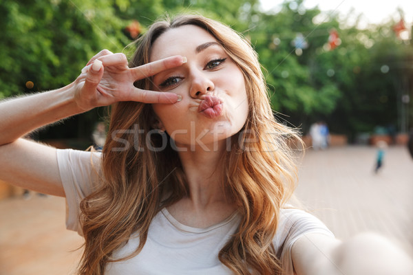 Close up of a pretty young girl taking selfie Stock photo © deandrobot