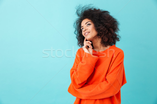 Thoughtful american woman in colorful shirt looking upward with  Stock photo © deandrobot
