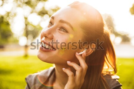 Cute fitness sports woman in park outdoors listening music with earphones. Stock photo © deandrobot