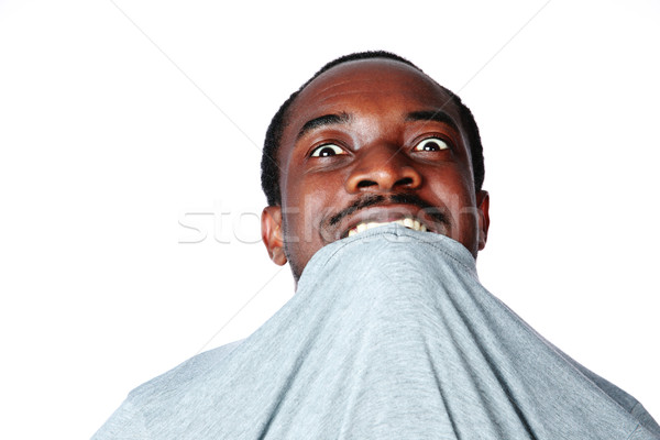 Portrait of crazy young african man biting his t-shirt over white background Stock photo © deandrobot