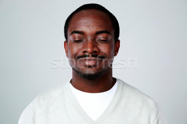 Portré boldog afrikai férfi csukott szemmel szürke Stock fotó © deandrobot