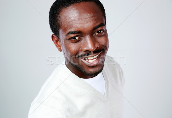 Portrait of a smiling african man on gray background Stock photo © deandrobot