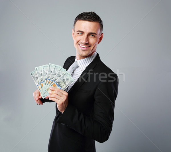 Cheerful businessman holding group of dollar bills on a gray background Stock photo © deandrobot