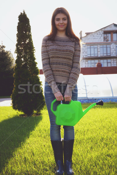 Portrait of a happy woman holding watering pot in garden Stock photo © deandrobot