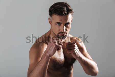 Portrait of a muscular man keeping his palms by face Stock photo © deandrobot