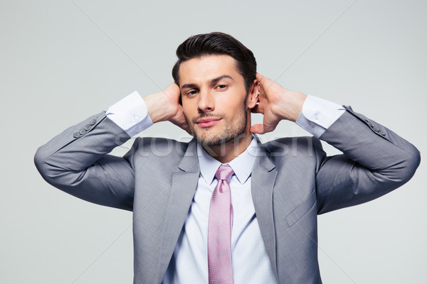 Portrait of a businessman covering his ears Stock photo © deandrobot