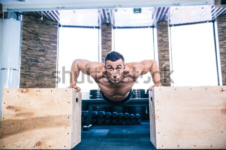 Muscular man doing push ups on fit box Stock photo © deandrobot