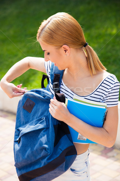 Happy female student closing her backpack outdoors Stock photo © deandrobot