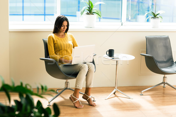Businesswoman sitting on office chair and using laptop Stock photo © deandrobot