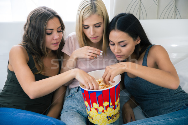 Three girlfriends eating popcorn Stock photo © deandrobot