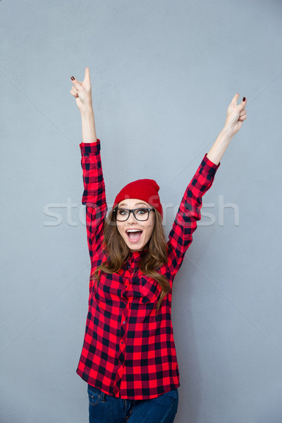Cheerful woman standing with raised hands up Stock photo © deandrobot