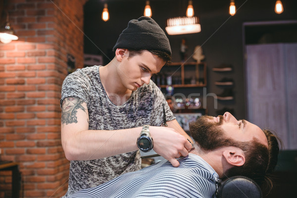Young barber shaving beard of his client with hair clipper Stock photo © deandrobot