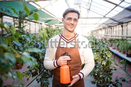 Handsome male gardener holding small tagerine tree in pot Stock photo © deandrobot
