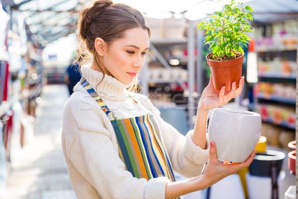 Thoughtful woman gardener choosing new pot in store Stock photo © deandrobot