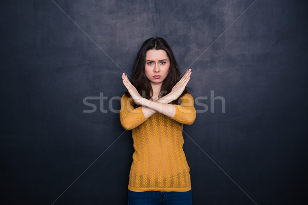 Serious woman showing stop sign with crossed palms Stock photo © deandrobot