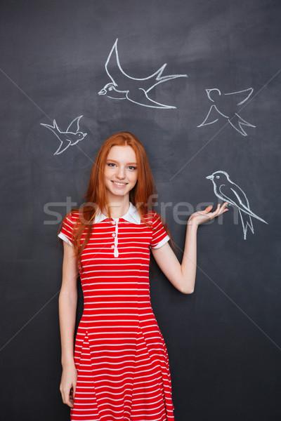 Beautiful woman holding drawn bird on blackboard background Stock photo © deandrobot