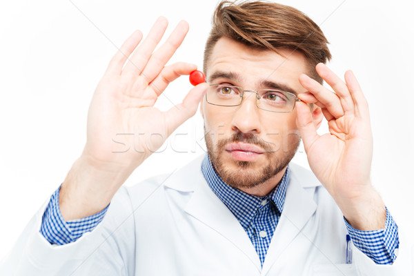 Male doctor in glasses looking on pill Stock photo © deandrobot