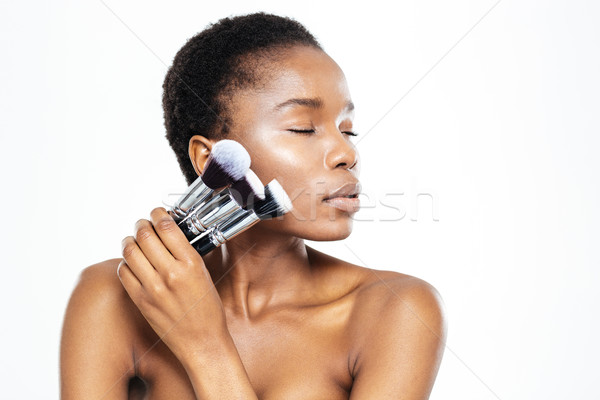 Afro american woman with closed eyes holding makeup brushes Stock photo © deandrobot