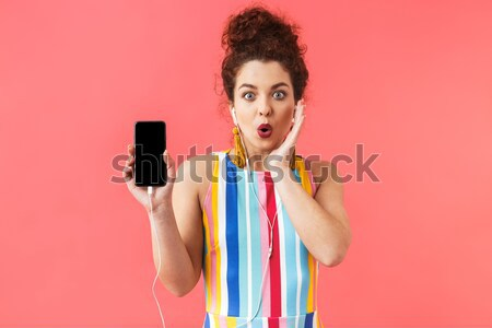 Smiling cute young woman showing ok gesture  Stock photo © deandrobot