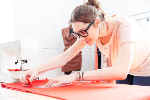 Focused woman tailor standing and drawing on red textile material Stock photo © deandrobot