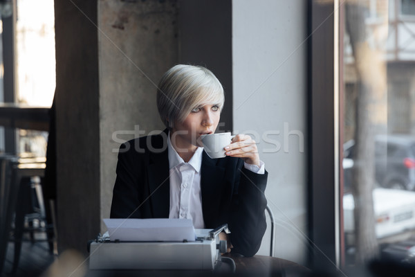 Beautiful blonde girl drinking coffee in modern cafe  Stock photo © deandrobot
