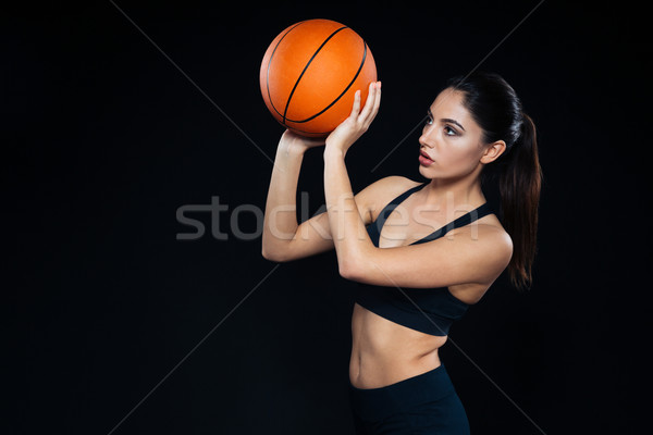 Focused pretty woman athlete standing and throwing basketball ball  Stock photo © deandrobot