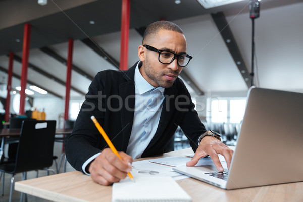 Young employee looking at computer monitor  Stock photo © deandrobot