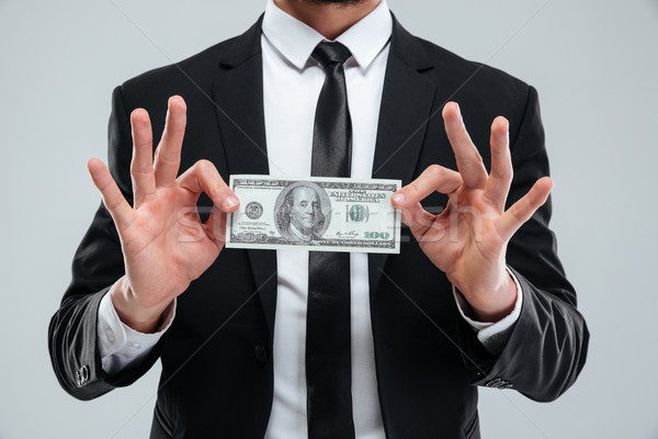 Businessman in suit and tie holding one hundred dollars banknote Stock photo © deandrobot