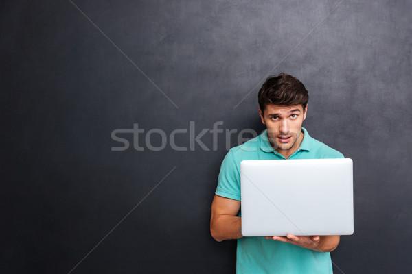Сток-фото: привлекательный · молодым · человеком · используя · ноутбук · доске · ноутбука