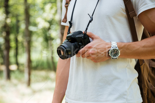 Man photographer holding modern photo camera in forest Stock photo © deandrobot