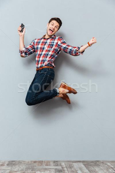 Feliz hombre escuchar música teléfono celular saltar excitado Foto stock © deandrobot