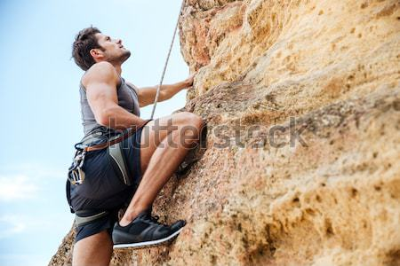 Young man climbing a steep wall in mountain Stock photo © deandrobot