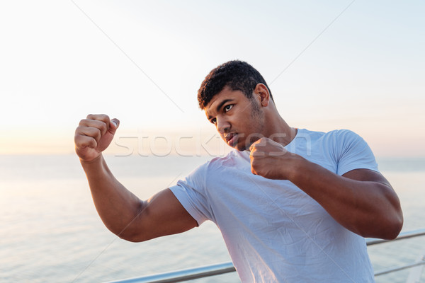 Handsome african man boxer doing exercises in the morning Stock photo © deandrobot