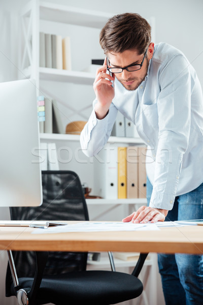 Businessman closing a deal signing documents at desk in office Stock photo © deandrobot