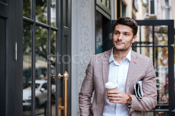 Man with coffee and newsaper walking along street in city Stock photo © deandrobot