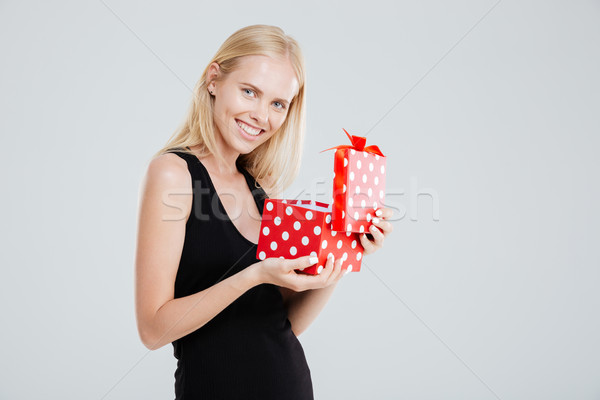 Portrait of a cheerful woman in dress opening gift box Stock photo © deandrobot