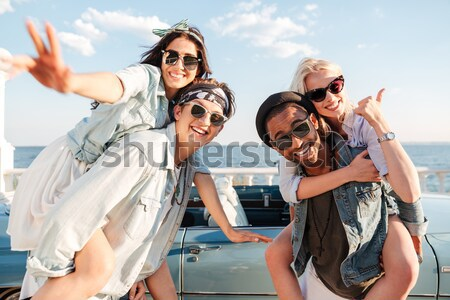 Two men carrying girls and having fun in summer Stock photo © deandrobot